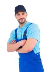 Smiling male handyman in coveralls standing arms crossed