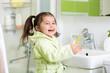 Smiling little girl brushing teeth in bath