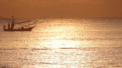 Fishing boat moves through the water at sunset.