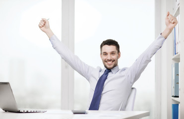 smiling businessman with laptop and documents
