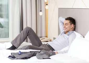 happy businesswoman lying in bed in hotel room