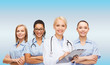 smiling female doctor and nurses with stethoscope