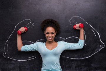 Smiling afro-american woman with dumbbells and painted arms on