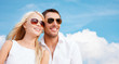 happy couple in shades over blue sky background