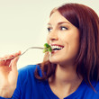 Portrait of young beautiful woman eating broccoli