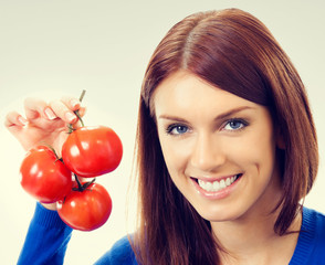 Portrait of young woman with tomatoes