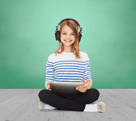 happy school girl with headphones and tablet pc