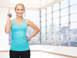 smiling woman with dumbbells flexing biceps in gym