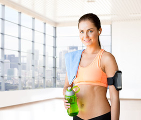 happy woman with bottle of water and towel in gym