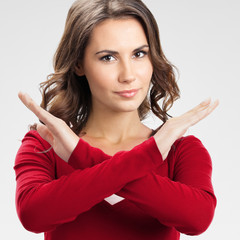 Serious woman with stop gesture, on grey