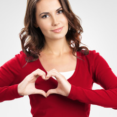 Woman showing heart symbol gesture, on grey