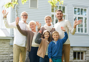 happy family waving hands in front of house