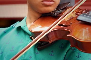 Musician playing violin melodically at the park