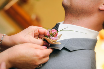 Mother putting a flower in the buttonhole of the groom dress