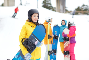 happy friends in helmets with snowboards