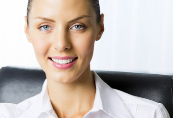 Cheerful smiling young businesswoman at office