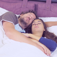 Cute couple sleeping hugged in bed in the morning