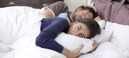 Sad desperate woman in bed while husband is sleeping