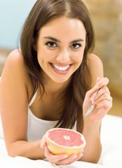 Portarit of young woman eating grapefruit