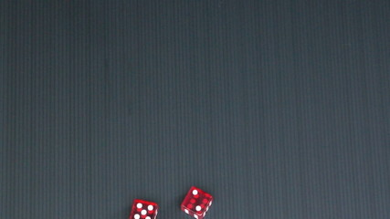 Two red dice fall on black surface