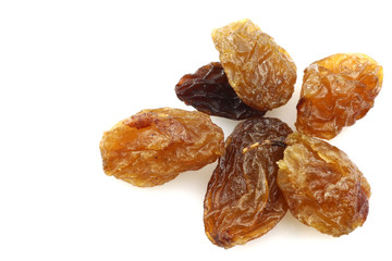 close up of a few dried raisins on a white background