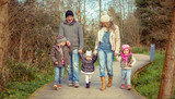Fototapety Happy family walking together holding hands in the forest