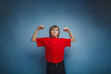 boy, teenager, twelve years in a red shirt, showing strength in