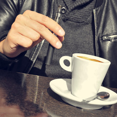 young man with an electronic cigarette and a cup of coffee in th
