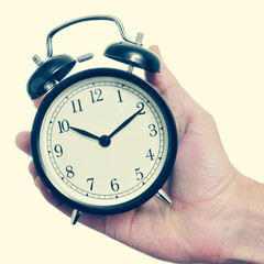 man hand holding a mechanical alarm clock, with a retro effect