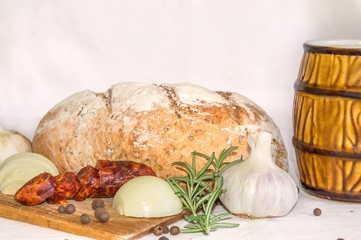 Loaf of bread with beer on white background