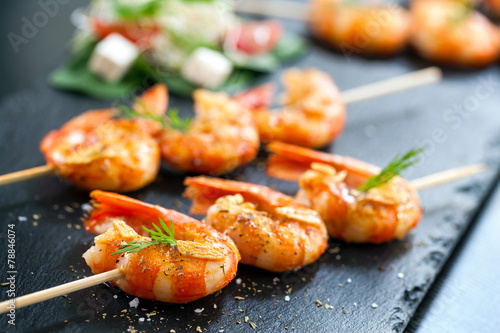 Leinwandbild Motiv Appetizing grilled prawns on skewer.