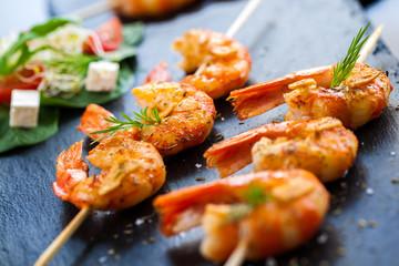 Roasted shrimp starter on skewer.