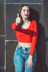 Young beautiful girl in red blouse showing thumbs up
