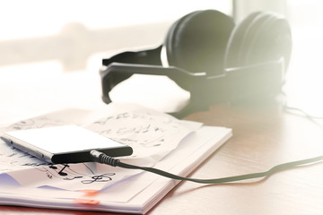 Closeup of smartphone with headphone on musical notes paper with