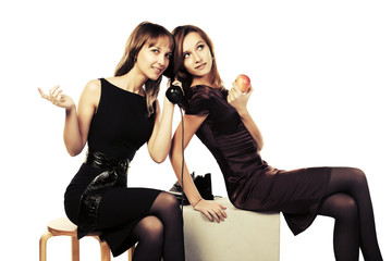 Two happy young fashion women calling on retro phone