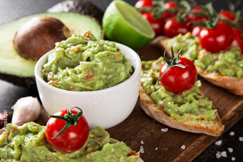 Leinwanddruck Bild Guacamole with bread and avocado