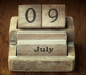 A very old wooden vintage calendar showing the date 9th July on