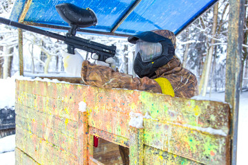 Man shooting from paintball gun behind wooden fortification