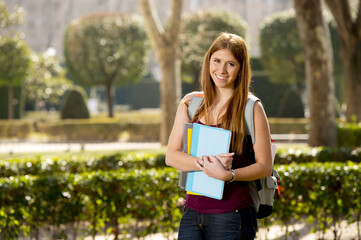 young cute student girl in university campus park with books