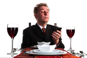 Geschäftsmann beim Essen schaut auf Smartphone