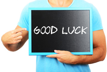 Man holding blackboard in hands and pointing the word GOOD LUCK