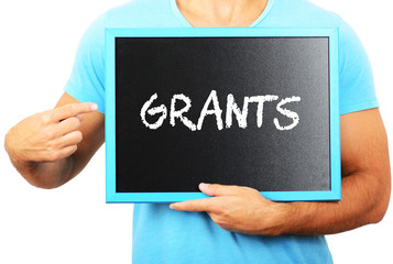 Man holding blackboard in hands and pointing the word GRANTS