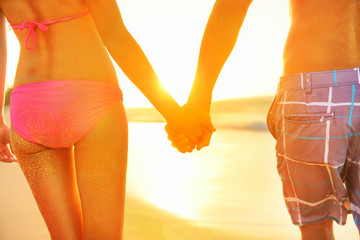 Holding hands couple in swimwear at beach