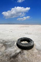 Abandoned tyre on salt sea shore