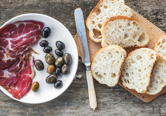 Smoked meat or prosciutto and olives on a white plate