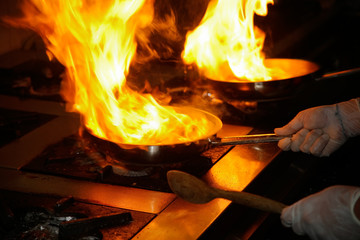 Flambe sauce pan on restaurant kitchen