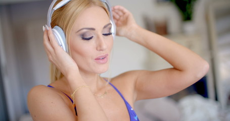 Attractive young blond woman listening to music
