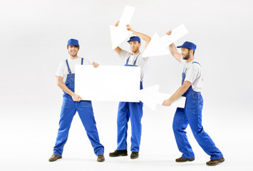 Three cheerful workers with empty banner