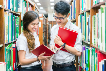 Asian couple of students in uniform at library
