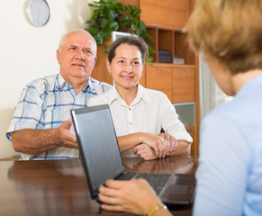 Senior couple with social worker at home